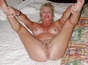 Reife blonde Frau macht ihre Beine breit